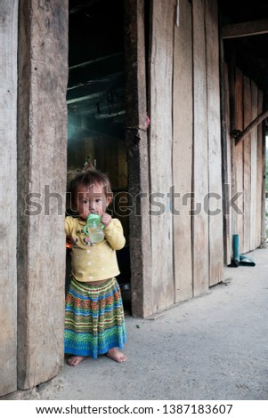 Lai Chau / Viet Nam - April 29th 2019 : Ethnic kid standing in front of her house in Lai Chau province