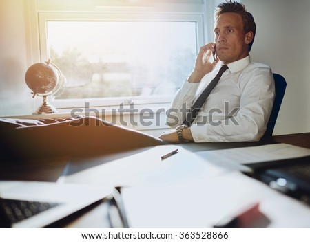 Laid back confident business man sitting at his desk with feet up talking on phone with documents on his desk