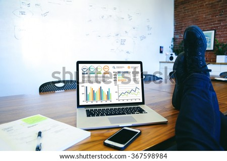 Laid back man putting feet up on table with a laptop showing business graphic charts.