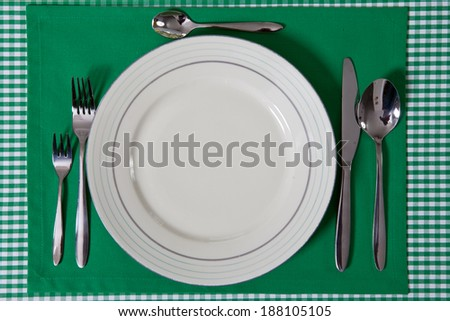laid table/ fork and spoon laid on green cloth in the kitchen