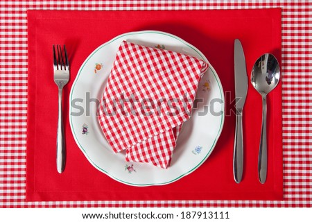 laid table/ fork and spoon laid on red cloth in the kitchen