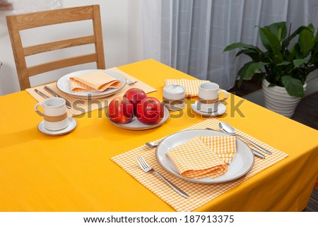 laid table/ fork and spoon laid on yellow cloth in the kitchen