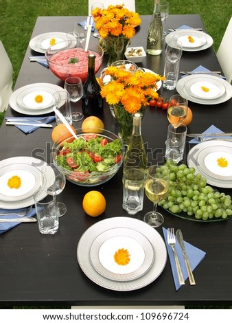Laid table on green grass in garden