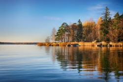 Lake and autumn trees. Colorful autumn landscape. Autumn forest reflected in water. Nature background.