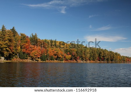 Lake and autumn trees reflecting on calm water, in Ontario, Canada