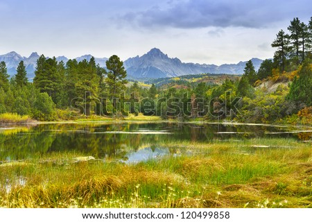 lake and mountain with golden and green trees in colorado during fall