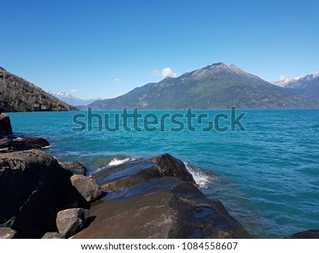 Lake and Mountains Landscape View with Clear Blue Sky in Patagonia Forest #1084558607