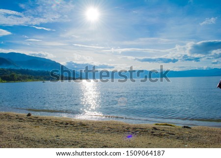 Lake Atitlan white sand beach beautiful sunrise and sunrise from the summits of the great mountains, hills with immense forests, fogs and clouds coming out of the big trees