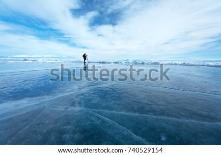 Lake Baikal in the winter. Silhouette of a lonely photographer against the background of an endless ice desert #740529154