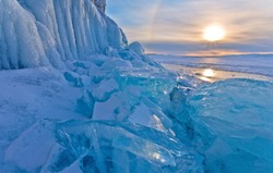 Lake Baikal is a cold winter afternoon. Blue ice hummocks near the icy cliffs of Olkhon Island at sunset