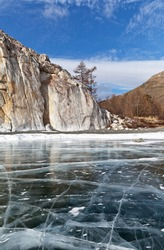 Lake Baikal on a sunny day in February. Beautiful winter landscape with clear transparent ice near the cliffs of the famous Cape Sagan-Zaba with ancient rock paintings. Ice travel. Natural background