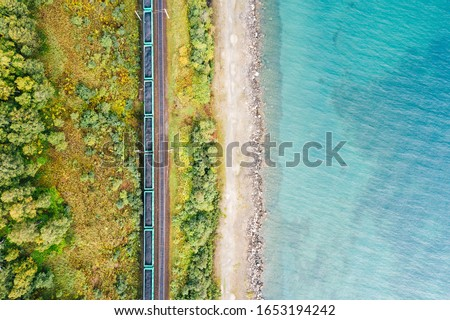 Photo of  Lake Baikal shore with green forest trees and turquoise water, aerial top down view. Freight train with coal on railroad of Trans-Siberian Railway. East Siberian Railway in Buryatia, Siberia, Russia