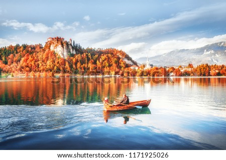Lake Bled in Slovenia. Romantic couple paddling wooden boat at the background of captivating seasonal autumn landscape, forest with yellow leaves and old castle on hill. Famous and popular landmark. #1171925026