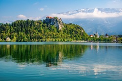 Lake Bled with the rocktop castle and St Martin church reflected in the water at sunny spring morning. Slovenia