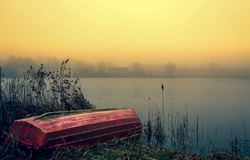Lake boat in sunrise fog. Boat on shore in sunrise fog. Sunrise lake boat view. Lake boat sunrise scene