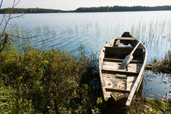 Lake boat of the old sample on the forest lake. The boat is made by Veps in the north-east of Russia. Even 30 years ago, such boats were hollowed out of the trunk of an old aspen tree