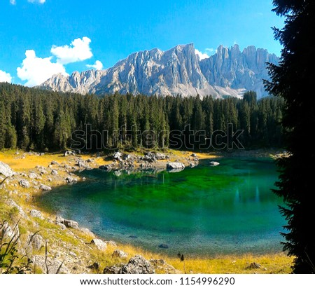 Lake Carezza or Karersee, a small emerald green mountain lake in the Dolomites in South Tyrol, Italy, in which Mt Catinaccio and the Latemar Group are reflected #1154996290