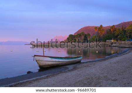 Lake Chapala in Jalisco Mexico glows in morning dawn with fishing boat on shore and pier and mountains in distance