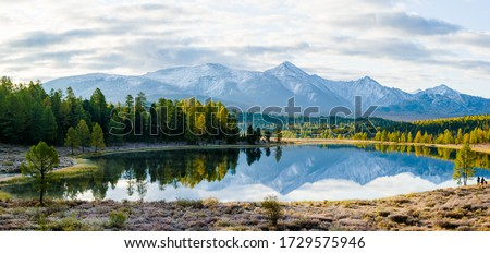 Lake Cicely Altai, Siberia, cloudy autumn day. Taiga, beautiful sky, haze, mountains with snow peaks, panorama.