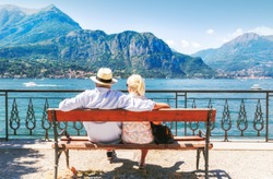 Lake Como, Italy. Senior couple resting at wooden bench by famous and popular travel destination - lake Como in Italy, with captivating view on mountains and tranquility of water surface.