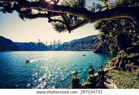 Lake Como. People on a boat ride on the lake. Summer time. European vacation, living life style, architecture and travel concept.. Vintage post processed