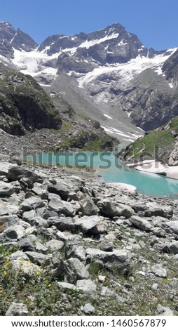 lake coverd by snow capped mountains with blue water beautifil pic ..charming sunny day tulyan lake for u  kashmir india