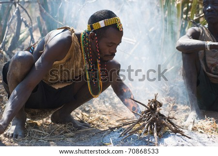 LAKE EYASI, TANZANIA - AUGUST 14: an unidentified man from Hdza tribe light a fire as they did thousands of years ago, on August 14, 2010. Hdza tribe is an ethnic group in north Tanzania