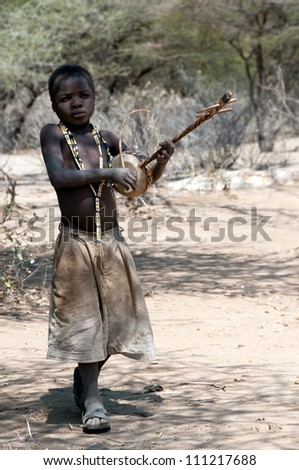 LAKE EYASI, TANZANIA - FEB 22: an unidentified man from Hadza tribe, shooting with an bow, on feb 22, 2012. Hadza people are an ethnic group in north Tanzania, who live hunting wild animals.