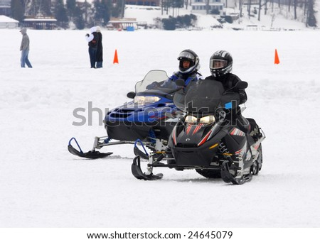 LAKE GEORGE, NY - February 7, 2009: A couple snowmobile riders exit the ice on Lake George in order to enjoy the February 7 , 2009 Lake George Winter Carnival.