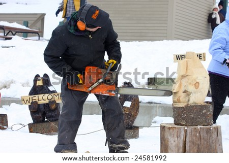 LAKE GEORGE, NY - February 7, 2009: A local artist carves a wooden bear out of a solid block of wood using a chainsaw at the February 7 , 2009 Lake George Winter Carnival.