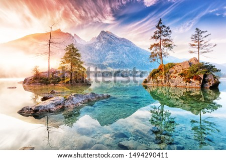Lake Hintersee in Germany, Bavaria, National Park Ramsau in Alps. Beautiful autumnal Alpine landscape, amazing light during sunrise. Incredible seasonal autumn scenery. Famous landmark in Germany.