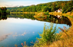 Lake house on the shore of the autumn forest. Autumn lake in forest. Lake house in autumn scene