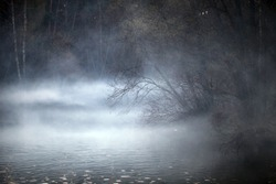 lake in the fog in an autumn forest