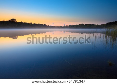 Lake in the mist at sunset