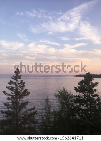 Lake in Two Harbors, MN in 2017. Sunset and tall, tall trees.  #1562641711