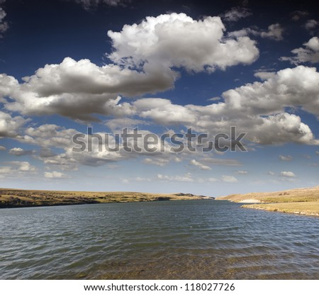 Lake - lake in Alberta's prairies with clouds and blue sky (Chain Lakes Prov.Park in Alberta, Canada) #118027726