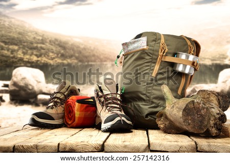 lake landscape and big backpack with shoes