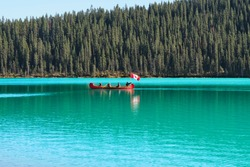 Lake Louise canoeing. Red boat with people holding Canadian flag canoeing in Lake Louise. Banff National Park. Canadian Rockies. Alberta. Canada