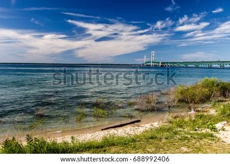 Lake Michigan Beach And Mackinac Beach. The blue waters of Lake Michigan with the landmark Mackinaw Bridge at the horizon. The suspension bridge connects the Upper and Lower Peninsula of Michigan.