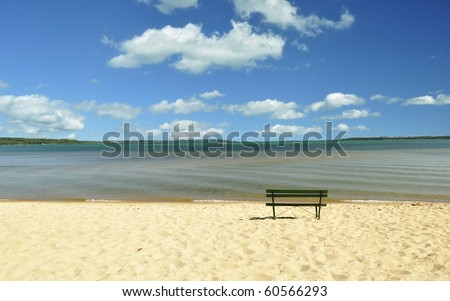 lake Michigan beach with bench and cloudy sky