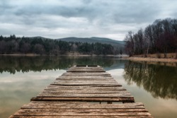 Lake pier at evening with hills on background. Reflection of the forest in the green water with blue cloudy sky. Pond at the forest. Small lake inrecreational area (Slovakia - Duchonka)