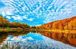 Lake reflecting sky in autumn landscape