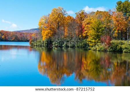 Lake reflections of fall foliage. Colorful autumn foliage casts its reflection on the calm waters of a North Carolina lake along the Blue Ridge Parkway.