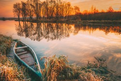 Lake River And Old Wooden Blue Rowing Fishing Boat At Beautiful Sunrise In Autumn Morning. Autumn Peaceful Landscape.