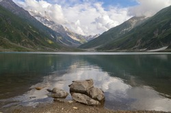 Lake Saiful Muluk reflects the mountains and the clouds in Kaghan Valley, Pakistan. The lake lies 3,224 m (10,578 ft) above sea level.