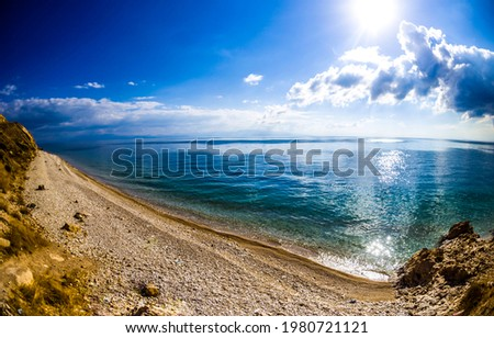 Lake shore at the foot of the mountain. Mountain lake beach landscape. Lake beach in mountains