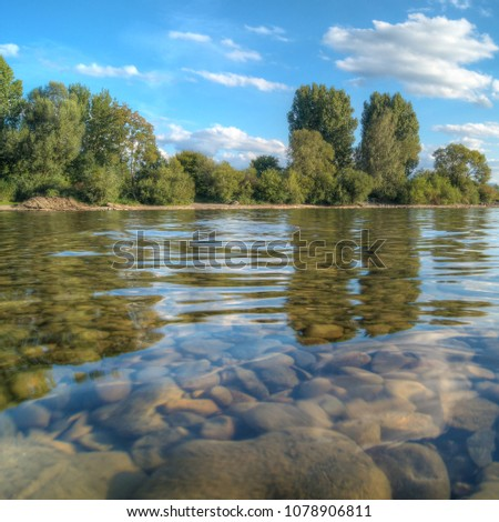 Lake shore with green trees and shallow water with stones under blue sky with some clouds; Local recreation area; Natural spaces at lakeshore  #1078906811