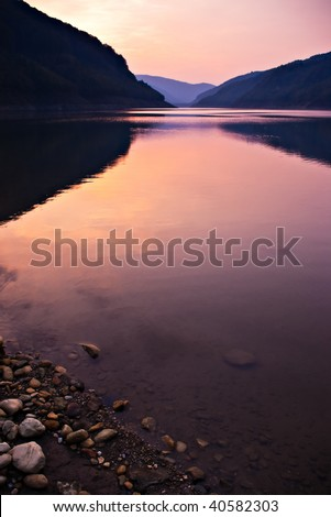 lake shore with stones after sunset