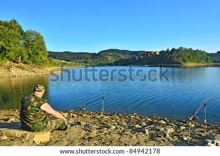 Lake Solina (Bieszczady, Poland) - senior fisherman angling - stock photo