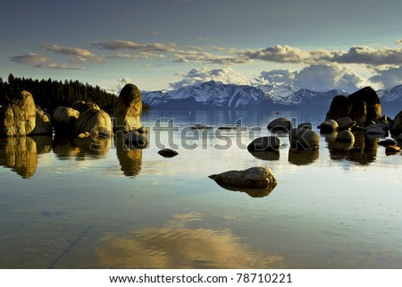 Lake Tahoe,  Zephyr Cove with calm blue water large rocks in the water with Mountains in the background